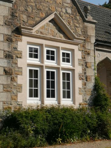 White PVCu windows into stone pillars